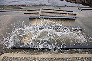 drain with water rushing out in to the river