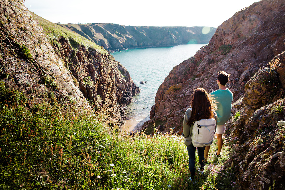 Couple exploring the cliff paths and enjoying the view out to sea and down to the hidden cove Plemont beach, Jersey, Channel Islands