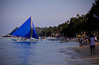 Blue sailboat on the bay just off White Sand Beach, Boracay, Philippines.