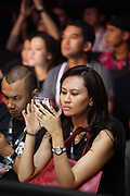 """Spectator on telephone at fight<br /><br />MMA. Mixed Martial Arts """"Tigers of Asia"""" cage fighting competition. Top professional male and female fighters from across Asia, Russia, Australia, Malaysia, Japan and the Philippines come together to fight. This tournament takes place in front of a ten thousand strong crowd of supporters in Pelaing Stadium. Kuala Lumpur, Malaysia. October 2015"""