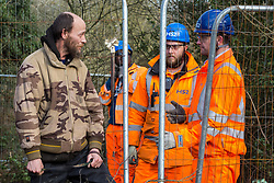 Harefield, UK. 7 February, 2020. An activist monitors HS2 engineers erecting Heras fencing to surround three environmental activists from Extinction Rebellion who have climbed a veteran oak tree close to the Harvil Road wildlife protection camp in order to try to protect it from felling. HS2 are expected to try to fell large numbers of mature trees in the immediate vicinity over the weekend even though the high-speed rail link is still awaiting Boris Johnson's approval.