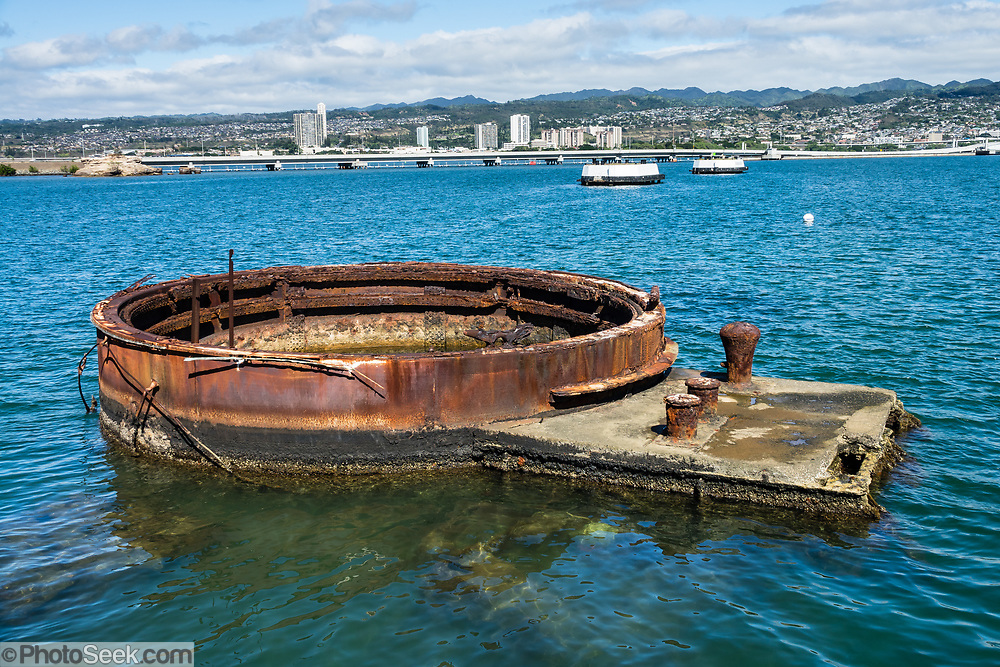 Aboard the USS Arizona Memorial, contemplate the rusting gun turret #3 of USS Arizona, sunk on 7 December 1941, yet still leaking oil, in Pearl Harbor, Oahu, Hawaii, USA. The USS Arizona Memorial marks the watery grave of 1102 sailors and Marines killed onboard that battleship during the Japanese surprise attack on Pearl Harbor, 7 December 1941. The attack united a divided America to join World War II. In one of history's greatest salvage jobs, all but 3 of the 21 ships sunk or damaged at Pearl Harbor were repaired back into service (only the USS Arizona was unsalvageable, whereas the Oklahoma and Utah were judged obsolete). More than two million people per year visit the 1962 USS Arizona Memorial, which is part of  the World War II Valor in the Pacific National Monument, run by the National Park Service. Reached only via boat, the memorial straddles but doesn't touch the sunken hull. USS Arizona (BB-39) was a Pennsylvania-class battleship launched by the United States Navy in 1916. A Japanese bomb violently exploded a powder magazine and sank the ship, killing 1177 officers and crewmen. The undersea wreck is a National Historic Landmark.