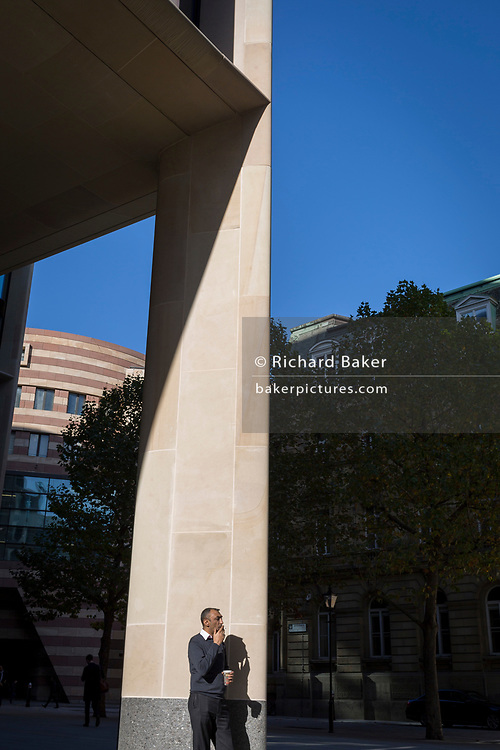 A City worker takes a drag on his cigarette while standing in autumn sunshine outside the new Bloomberg offices in Cannon Street, on 27th October 2017, in the City of London, England.