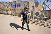 """04 FEBRUARY 2009 -- A shotgun toting deputy watches over undocumented immigrants being marched to Tent City. Maricopa County Sheriff Joe Arpaio marched about 200 undocumented immigrants in the Durango Jail to """"Tent City"""" where he will house the prisoners until or if they are deported. PHOTO BY JACK KURTZ"""