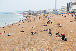 © Licensed to London News Pictures. 23/06/2019. Brighton, UK. Despite the lack of sunshine, a handful of people enjoy the hot weather by spending time on the beach in Brighton and Hove. Photo credit: Hugo Michiels/LNP