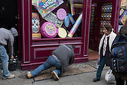 A workman props himself with an extended leg, beneath the display of a sweets shop, on 15th February 2017, in London, United Kingdom.