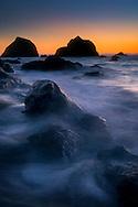 Sunset light over seastacks and coastal rocks on beach at False Klamath Cove, Redwood National Park, California