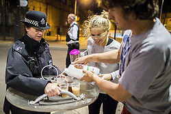 © Licensed to London News Pictures . 09/08/2011 . London , UK . Philippa Morgan-Walker (25, centre) and her husband, Jonny Walker (31, right) make tea for the police who are protecting their street , using a riot shield as a tea-tray. Some of the officers have been on duty for more than 30 hours . Police in Camden Town during a 3rd night of rioting and looting in London , which followed a protest against the police shooting of Mark Duggan in Tottenham . Photo credit : Joel Goodman/LNP