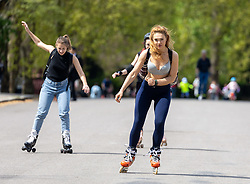 Licensed to London News Pictures. 09/05/2021. London, UK. Rollerblader Elia Bardashevich finally get to enjoy some sunshine in Kensington Gardens, London with her friends. The Met Office predict bbq weather today (Sunday) with temperatures hitting over 21c in London and the South East as the miserable May weather starts to warm up. Photo credit: Alex Lentati/LNP