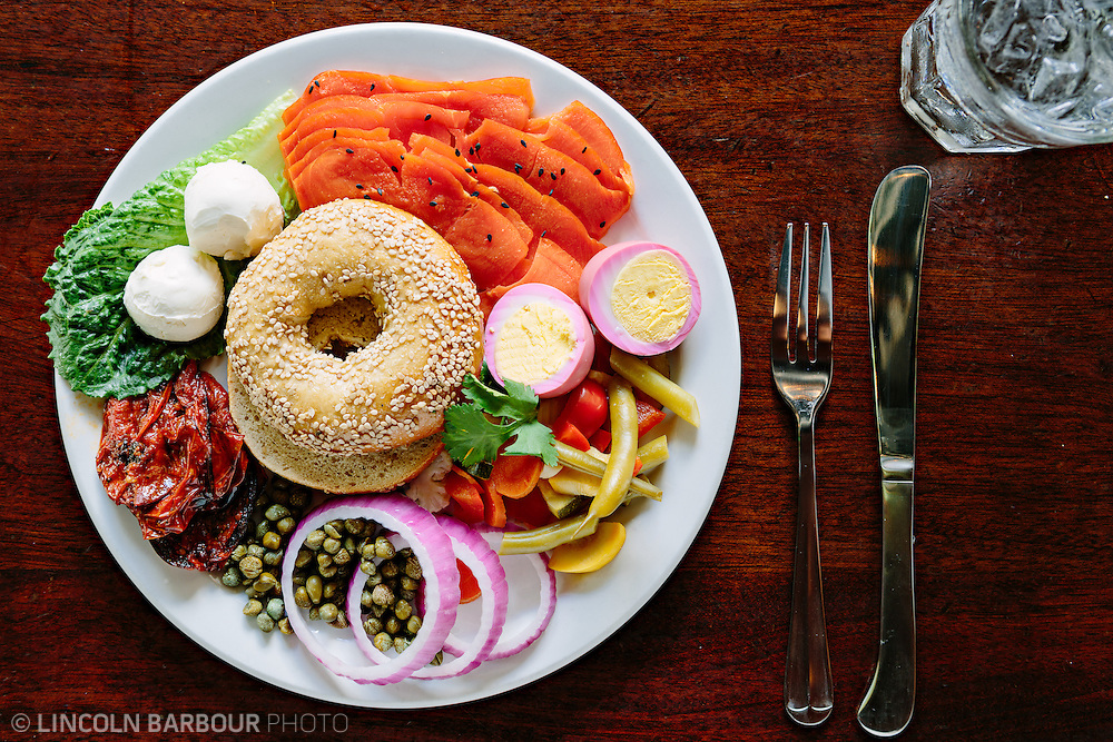 A top down view of a bagel sitting in the middle of a plate adorned with pickled vegetables, pickled egg, cream cheese, and lox.