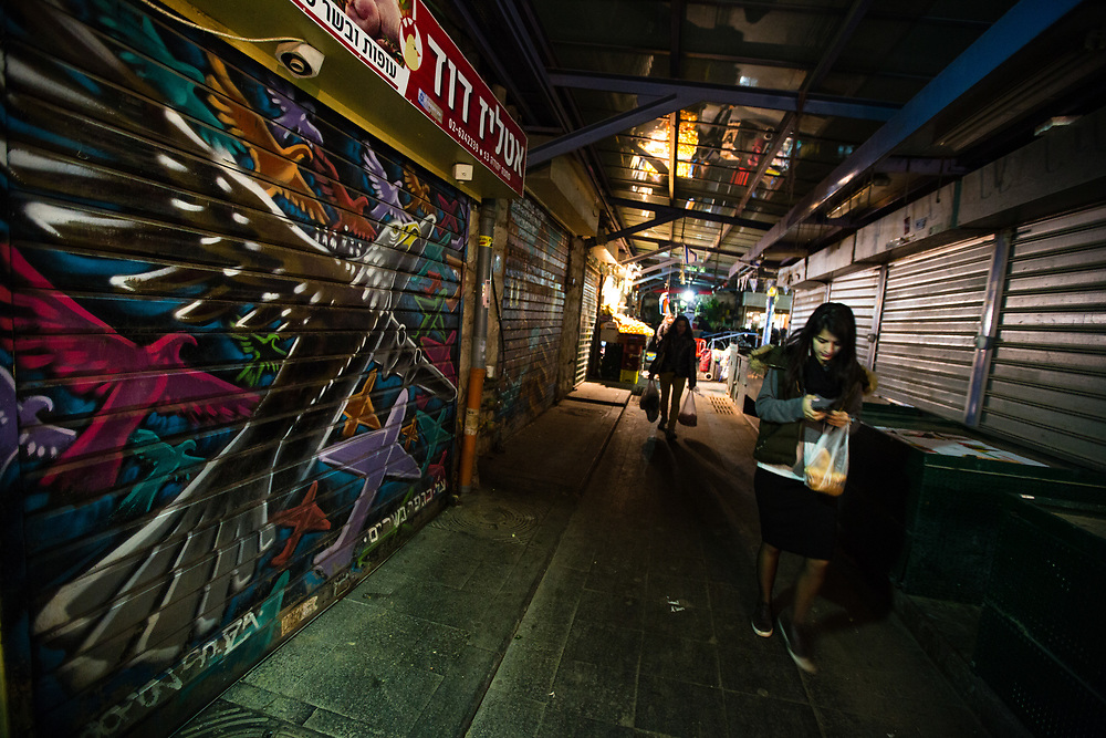 Shoppers pass in front of a graffiti depicting fanciful animals which was painted over a closed shutter at the Mahane Yehuda Market, often called 'The Shuk' in Jerusalem, Israel, on February 24, 2016.