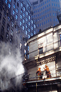 Two men in orange cleaning the outside of an apartment building