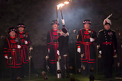 "© Licensed to London News Pictures. 05/11/2018. LONDON, UK. Yeoman Warders, former servicemen and women, ceremonially light the first flame followed by volunteers proceeding to light the rest of the installation, gradually creating a circle of light, radiating from the Tower.  A new installation by designer Tom Piper called ""Beyond the Deepening Shadow: The Tower Remembers"", is now open for the public to view at the Tower of London until Armistice Day 2018.  The moat is filled with thousands of individual flames commemorating the centenary of the end of the First World War.   Photo credit: Stephen Chung/LNP"