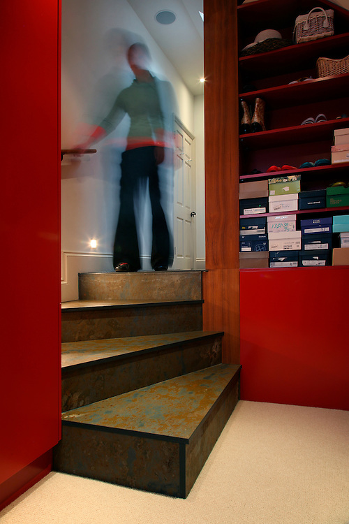 interior metal steps in plush bedroom with red cupboard full of shoe boxes and blurred figure walking through