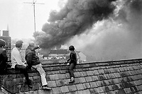 Rooftop spectators get a grandstand view of the huge fires resulting from the fifteen Provisional IRA bombs planted in premises in Bangor Co Down, N Ireland, 4th April 1974. 197404040215g<br /> <br /> Copyright Image from Victor Patterson, 54 Dorchester Park, Belfast, UK, BT9 6RJ<br /> <br /> t1: +44 28 9066 1296 (from Rep of Ireland 048 9066 1296)<br /> t2: +44 28 9002 2446 (from Rep of Ireland 048 9002 2446)<br /> m: +44 7802 353836<br /> <br /> victorpattersonbelfast@gmail.com<br /> victorpatterson@me.com<br /> <br /> www.victorpatterson.com<br /> <br /> Please see my Terms and Conditions of Use at https://www.victorpatterson.com/page2<br /> It is IMPORTANT that you familiarise yourself with them.<br /> <br /> Images used on the Internet incur an additional cost and must be visibly watermarked i.e. © Victor Patterson within the body of the image and copyright metadata must not be deleted. Images used on the Internet have a size restriction of 4kbs and are chargeable at rates available at victorpatterson.com.<br /> <br /> This image is available only for the use of the download recipient i.e. television station, newspaper, magazine, book publisher, etc, and must not be passed on to any third party. It is also downloaded on condition that each and every usage is notified within 7 days to victorpatterson@me.com<br /> <br /> The right of Victor Patterson (or the named photographer) to be identified as the author is asserted in accordance with The Copyright Designs And Patents Act (1988). All moral rights are asserted.