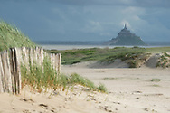 The historic Mont St Michel, topped with its 11th century abbey, seen from the beach in Genêts, France.