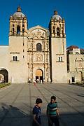 Santo Domingo de Guzmán Church exterior shot, with two young Mexican men in the foreground, Oaxaca City, Mexico.