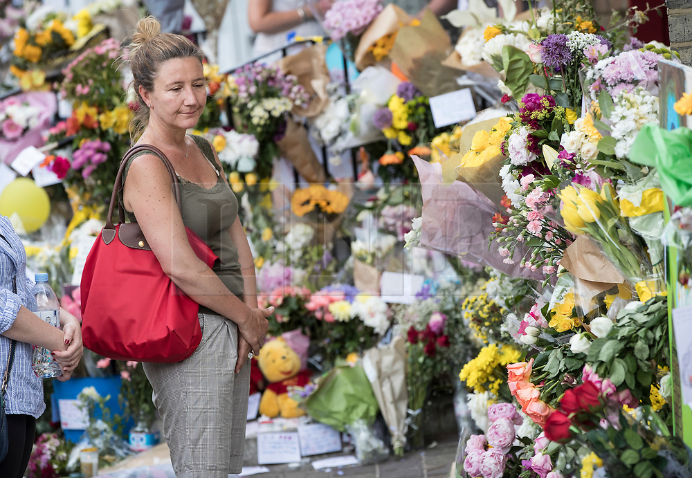 © Licensed to London News Pictures. 18/06/2017. London, UK. A woman looks at floral tributes placed outside a church near the remains of the burnt out Grenfell tower block . The blaze engulfed the 27-storey building killing dozens - with 34 people still in hospital, many of whom are in critical condition. The fire brigade say that they don't expect to find anyone else alive. Photo credit: Peter Macdiarmid/LNP