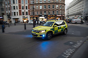 An ambulance passes at high speed with blue lights flashing in central London, England, United Kingdom. People and vehicles clear out of the way for all emergency service vehicles.