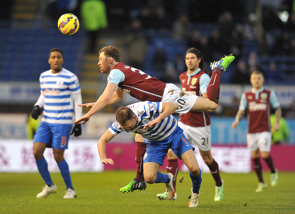 Burnley's Ashley Barnes falls over Queens Park Rangers' Clint Hill in order to get to the ball<br /> <br /> Photographer Dave Howarth/CameraSport<br /> <br /> Football - Barclays Premiership - Burnley v Queens Park Rangers - Saturday 10th January 2015 - Turf Moor - Burnley<br /> <br /> © CameraSport - 43 Linden Ave. Countesthorpe. Leicester. England. LE8 5PG - Tel: +44 (0) 116 277 4147 - admin@camerasport.com - www.camerasport.com