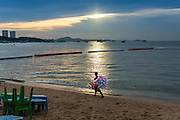 """26 SEPTEMBER 2014 - PATTAYA, CHONBURI, THAILAND: A vendor who sells toys walks along Pattaya Beach at the end of the day. Pataya, a beach resort about two hours from Bangkok, has wrestled with a reputation of having a high crime rate and being a haven for sex tourism. After the coup in May, the military government cracked down on other Thai beach resorts, notably Phuket and Hua Hin, putting military officers in charge of law enforcement and cleaning up unlicensed businesses that encroached on beaches. Pattaya city officials have launched their own crackdown and clean up in order to prevent a military crackdown. City officials have vowed to remake Pattaya as a """"family friendly"""" destination. City police and tourist police now patrol """"Walking Street,"""" Pattaya's notorious red light district, and officials are cracking down on unlicensed businesses on the beach.     PHOTO BY JACK KURTZ"""