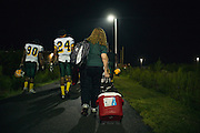 """BIRMINGHAM, AL – SEPTEMBER 11, 2015: Sonya Whitaker walks to the buses with the Woodlawn High School football team following a game. As a type 1 diabetic, Quintarius Monroe requires frequent blood sugar testing and supervision when self-administering insulin. When care from qualified personnel at his school in Center Point became unavailable, Monroe was forced to transfer several miles away from his locally zoned school to attend Woodlawn High School. The Americans with Disabilities Act requires schools to provide """"reasonable accommodation"""" for students with medical conditions, but given that most schools no longer retain school nurses, many schools are failing to provide adequate care for their students.<br /> CREDIT: Bob Miller for The New York Times"""