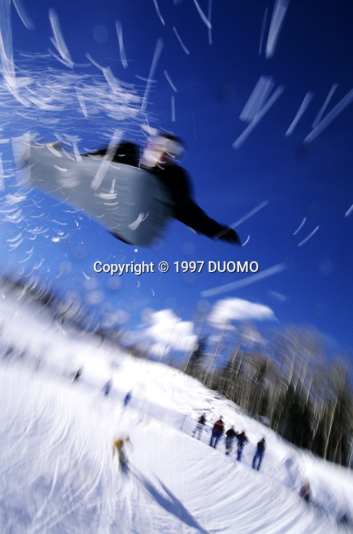Male snowboarder flying throught the air.