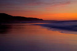 Bright orange sky at sunset on the beach in Morro Bay, California