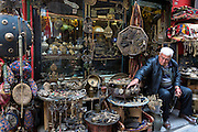 Shopkeeper with metal objects in antique shop in The Grand Bazaar, Kapalicarsi, great market, Beyazi, Istanbul, Turkey