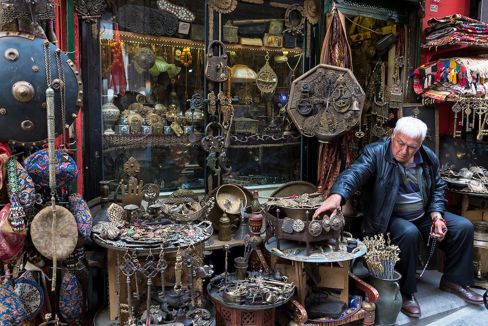 Shopkeeper with metal objects in antique shop in The Grand Bazaar, Kapalicarsi, great market, Beyazi, Istanbul, Turkey