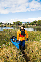 Portrait of kayaker while he takes boat out of Owens River and clouds move across the Eastern Sierras, California.