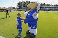 Haydon the Womble hiding the ball under his shirt from Mascot called Haydon during the EFL Sky Bet League 1 match between AFC Wimbledon and Shrewsbury Town at the Cherry Red Records Stadium, Kingston, England on 14 September 2019.