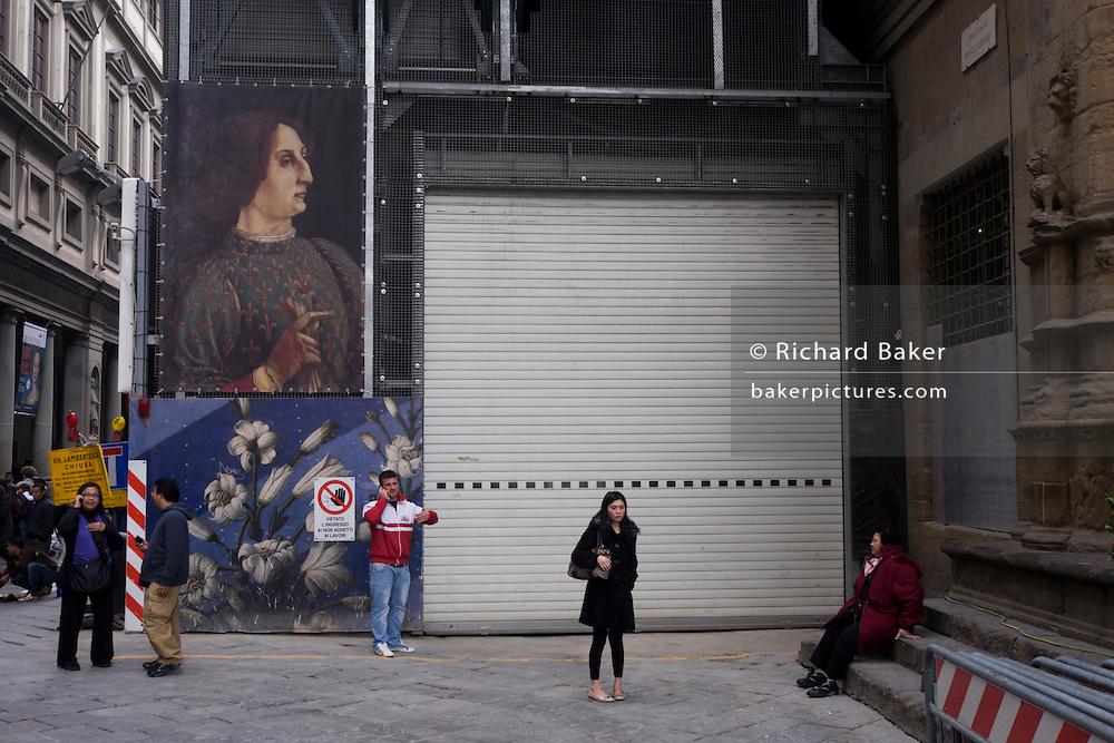 Tourists beneath renaissance art construction poster  in Florence's Piazza degli Uffizi. .