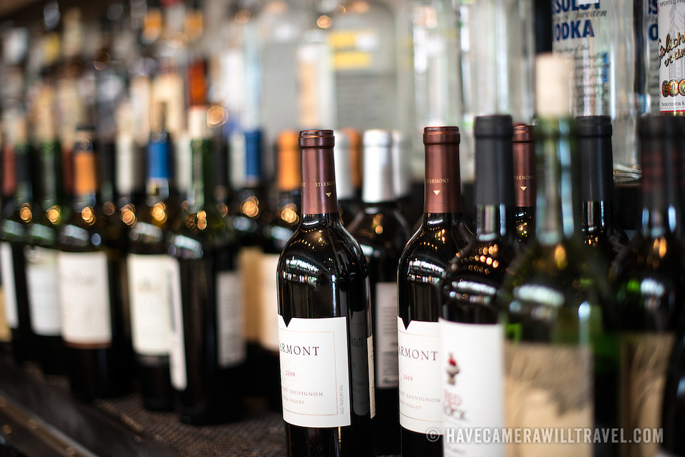 Wine bottles lined up behind a bar.