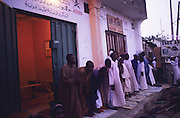 Frida night prayer. Local Hispah Sharia police offices. From here the volunteer police force recruits new members and surveys the neighborhood for anything considered non-Sharia..The implementation of Islamic Sharia Law across the twelve northern states of Nigeria, centres upon Kano, the largest Muslim Husa city, under the feudal, political and economic rule of the Emir of Kano. Islamic Sharia Law is enforced by official state apparatus including military and police, Islamic schools and education, plus various volunteer Militia groups supported financially and politically by the Emir and other business and political bodies. Fanatical Islamic Sharia religious traditions  are enforced by the Hispah Sharia police. Deliquancy is controlled by the Vigilantes volunteer Militia. Activities such as Animist Pagan Voodoo ceremonies, playing music, drinking and gambling, normally outlawed under Sharia law exist as many parts of the rural and urban areas are controlled by local Mafia, ghetto gangs and rural hunters. The fight for control is never ending between the Emir, government forces, the Mafia and independent militias and gangs. This is fueled by rising petrol costs, and that 70% of the population live below the poverty line. Kano, Kano State, Northern Nigeria, Africa