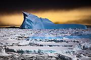 Dark storm cloud over blue iceberg and heavy pack ice, Penola Strait, Antarctic Peninsula.