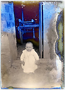 toddler standing by open barn door severely eroding glass plate early 1900s