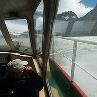 A tourist watches waves crash over windows on a boat on Grey Lake in Torres del Paine National Park, Chile.