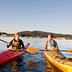 A man and woman sea kayaking near Sheep Porcupine Island in Maine's Acadia National Park.  Bar Harbor.