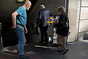 A lady carries a bouquet of flowers at the entrance of Monument underground station in the heart of the capital's financial district, on 19th April, in the City of London, England.