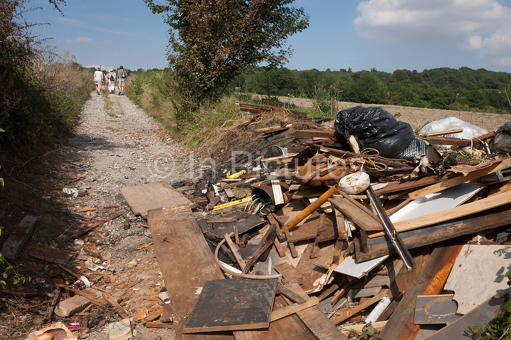 Countryside ramblers and a heap of dumped and burned fly-tipped waste on a footpath, on 27th August 2017, near Cobham, Kent, England.