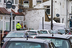 A couple, seemingly unable to leave their home where a forensic tent has been set up, talk to a police officer as forensics investigators conduct a fingertip search at the scene in Chalgrove Road, Tottenham, North London, where a seventeen year-old girl was shot dead on the evening of April 2nd. London, April 03 2018.
