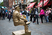 Street performer as a metallic painted balancing 'Living Statue' in Covent Garden delighting the gathered crowds. London, UK.