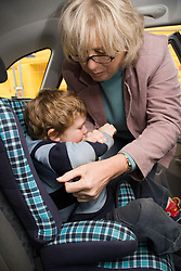 Grandmother strapping grandson into a car seat,