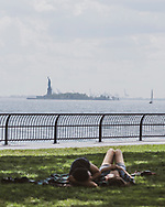 New York City, USA - July 6, 2016: A couple talks together while laying on a blanket on a beautiful summer day in lower Manhattan. The Statue of Liberty is in the distance.