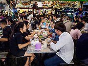 05 MARCH 2019 - BANGKOK, THAILAND:  Tourists eat stewed pork ribs in the Ratchada Night Market. The Ratchada Night Market is the newest night market in Bangkok. It was originally a small night market popular with local people but now is tourism destination. Most nights the market is jammed with foreign tourists.   PHOTO BY JACK KURTZ