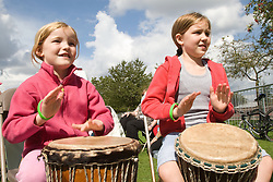 Two girls taking part in a drumming workshop at a Parklife summer activities event,