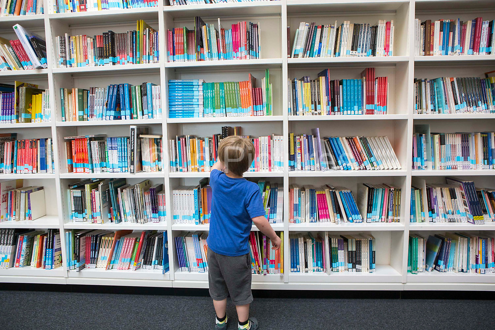 A child stands at one of book shelves with integrated lighting inside the library of the Hive in Worcester, UK. The first fully integrated university and public library in the UK. It houses the county archives and archaeology service, the local history centre and is also a local authority hub. The building is low energy.