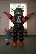 A girl tries to play with a robot display at the Bethnal Green Museum of Childhood, London, UK.