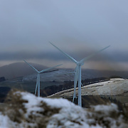 Wind turbines harnessing the wind in the Scottish Borders, 3rd of January 2021, Scotland, United Kingdom. The wind farm, Longpark Wind Farm, is long established and part of the renewable energy production in Scotland. The farm sits in the hills above the village Stow, near Galashields in the Scottish Borders. In between the wind turbines sheep grass in the fields lightly covered by snow.